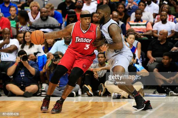 Al Harrington of Trilogy dribbles the ball while being guarded by Ivan Johnson of the Ghost Ballers during week six of the BIG3 three on three...