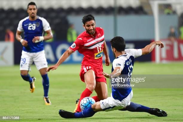 Al Hilal's defender Abdullah AlHafith tackles Persepolis' midfielder Sadegh Moharrami during the first leg of their AFC Champions League semifinal...