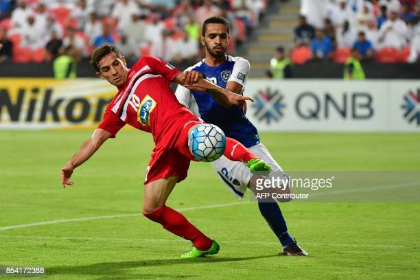 Al Hilal's defender Mohammed Alburayk vies for the ball with Persepolis' midfielder Farshad Ahmadzadeh during the first leg of their AFC Champions...