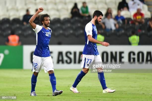 Al Hilal's defender Yasser AlShahrani celebrates alongside forward Omar Khribin after scoring during the first leg of their AFC Champions League...