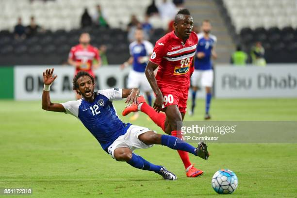 Al Hilal's defender Yasser AlShahrani falls as he vies for the ball with Persepolis' forward Godwin Mensha during the first leg of their AFC...