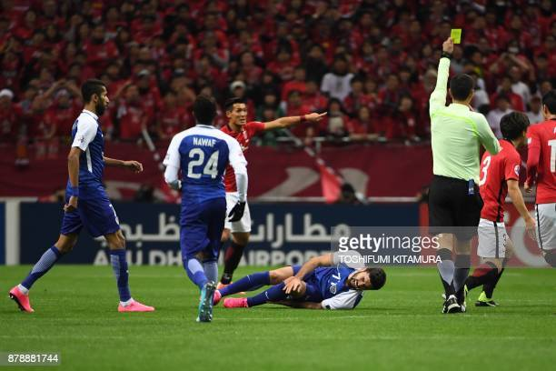 Al Hilal's forward Omar Khrbin lies on the pitch as the referee awards a yellow card during the second leg of the AFC Champions League football final...