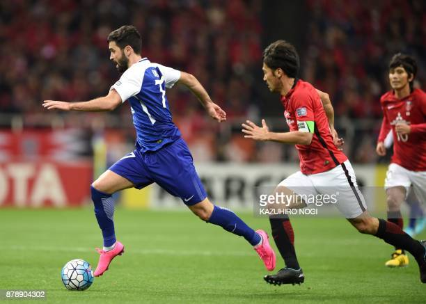 Al Hilal's forward Omar Khrbin runs with the ball past Urawa Red Diamonds' midfielder Yuki Abe during the second leg of the AFC Champions League...