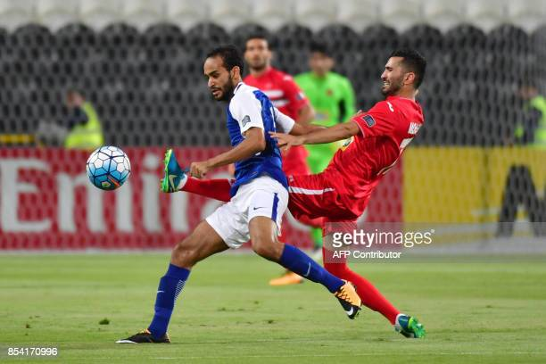 Al Hilal's midfielder Abdullah Otayf is tackled by Persepolis' midfielder Mohsen Mosalman during the first leg of their AFC Champions League...