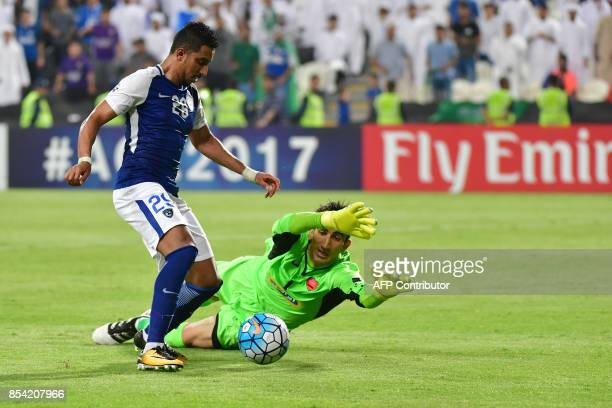 Al Hilal's midfielder Salem Aldawsari fights for the ball with Persepolis' goalkeeper from Ali Reza Safarbeiranvand during the first leg of their AFC...