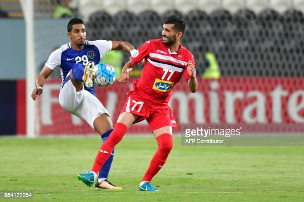 Al Hilal's midfielder Salem AlDawsari vies for the ball with Persepolis' midfielder Sadegh Moharrami during the first leg of their AFC Champions...