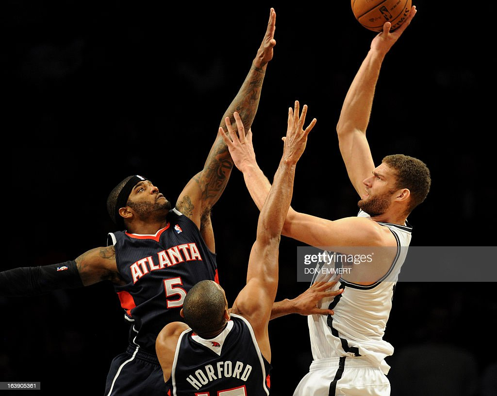 Al Horford (C) and Josh Smith (L) of the Atlanta Hawks guard Brooklyn Nets Brook Lopez March 17, 2013 at the Barclay Center in New York.