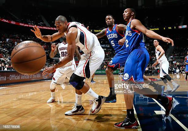 Al Horford of the Atlanta Hawks battles for a loose ball with Arnett Moultrie and Evan Turner of the Philadelphia 76ers at Philips Arena on March 6...