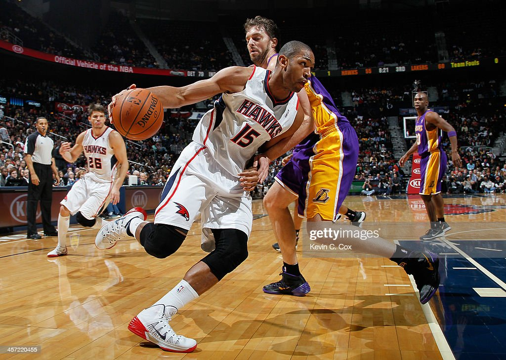 Al Horford #15 of the Atlanta Hawks draws a foul from Pau Gasol #16 of the Los Angeles Lakers at Philips Arena on December 16, 2013 in Atlanta, Georgia.