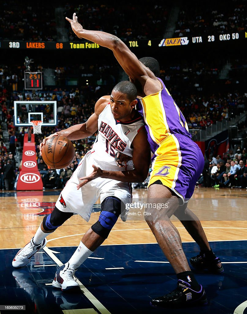 Al Horford #15 of the Atlanta Hawks drives against Metta World Peace #15 of the Los Angeles Lakers at Philips Arena on March 13, 2013 in Atlanta, Georgia.