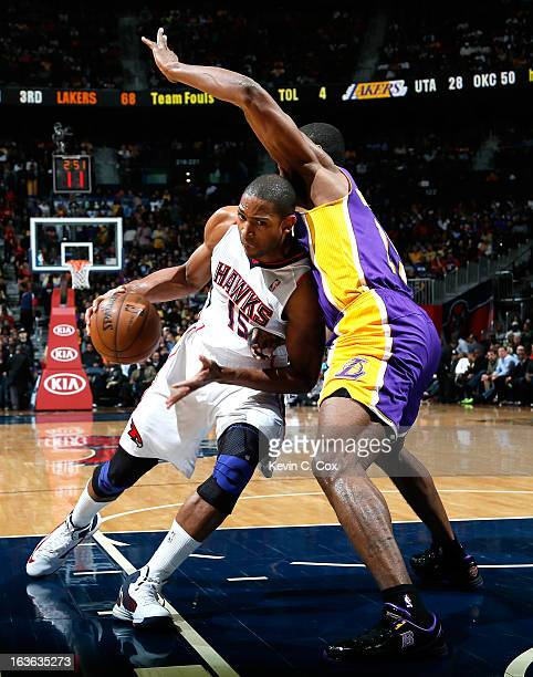 Al Horford of the Atlanta Hawks drives against Metta World Peace of the Los Angeles Lakers at Philips Arena on March 13 2013 in Atlanta Georgia NOTE...