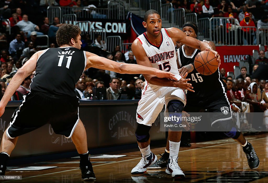 Al Horford #15 of the Atlanta Hawks drives between Brook Lopez #11 and Gerald Wallace #45 of the Brooklyn Nets at Philips Arena on January 16, 2013 in Atlanta, Georgia.