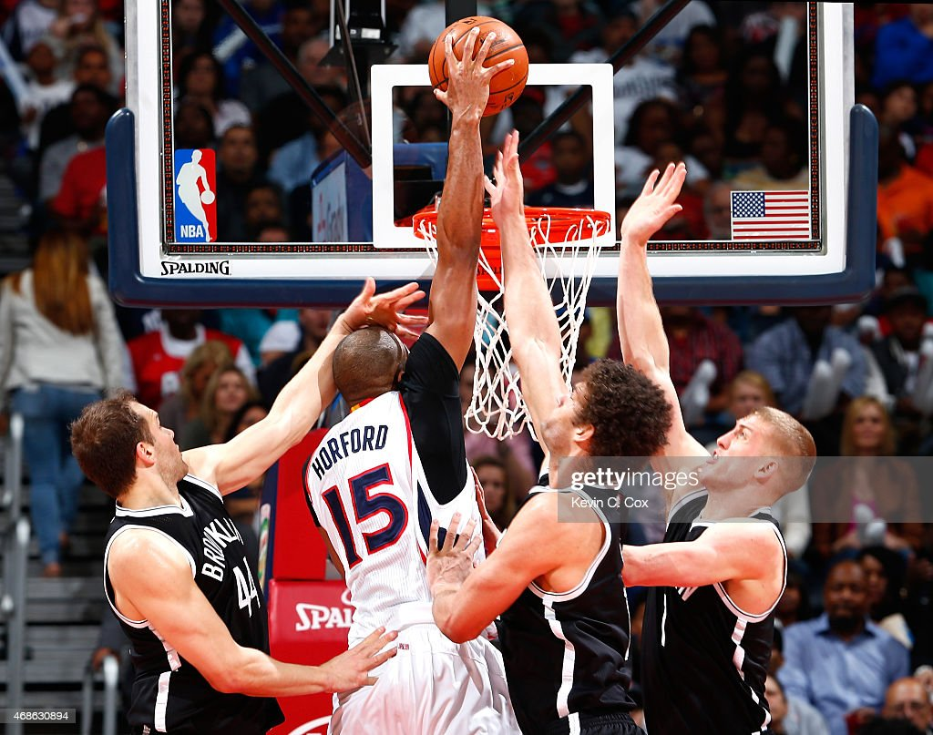 Al Horford #15 of the Atlanta Hawks dunks against Bojan Bogdanovic #44, Brook Lopez #11, and Mason Plumlee #1 of the Brooklyn Nets at Philips Arena on April 4, 2015 in Atlanta, Georgia.