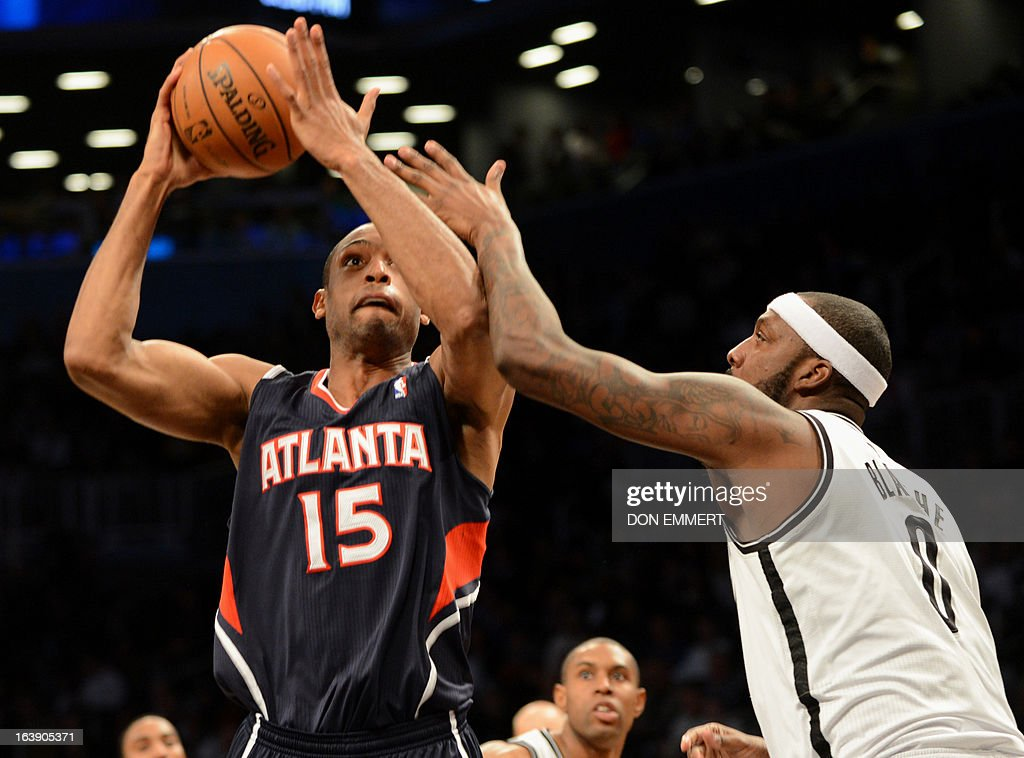 Al Horford(L) of the Atlanta Hawks gets a shot off past Brooklyn Nets Andray Blatche March 17, 2013 at the Barclay Center in New York.
