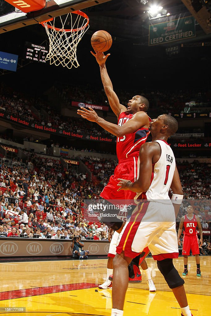 Al Horford #15 of the Atlanta Hawks goes to the basket against Chris Bosh #1 of the Miami Heat during a game between the Atlanta Hawks and the Miami Heat on December 10, 2012 at American Airlines Arena in Miami, Florida.