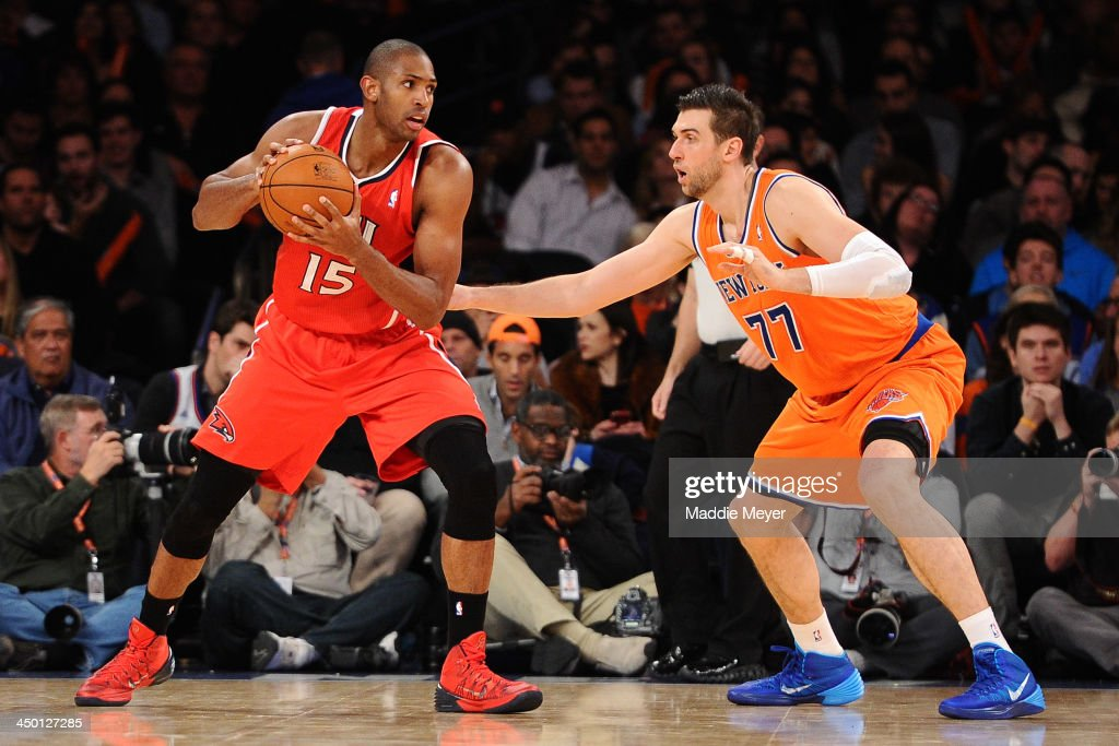Al Horford #15 of the Atlanta Hawks looks for a pass with pressure from Andrea Bargnani #77 of the New York Knicks at Madison Square Garden on November 16, 2013 in New York City. The Hawks defeat the Knicks 110-90.