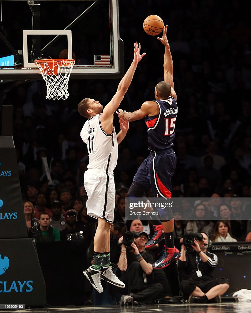 Al Horford #15 of the Atlanta Hawks scores two over Brook Lopez #11 of the Brooklyn Nets at the Barclays Center on March 17, 2013 in New York City. The Hawks defeated the Nets 105-93.