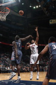 Al Horford of the Atlanta Hawks shoots against DeSagana Diop of the Charlotte Bobcats during a preseason game on December 22 2011 at Philips Arena in...