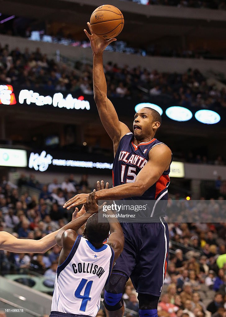 Al Horford #15 of the Atlanta Hawks takes a shot against Darren Collison #4 of the Dallas Mavericks at American Airlines Center on February 11, 2013 in Dallas, Texas.