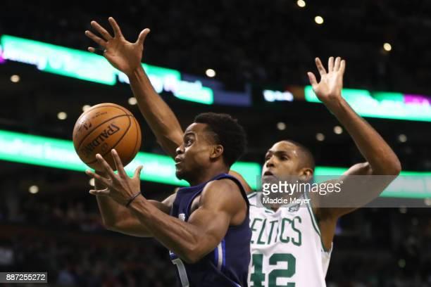 Al Horford of the Boston Celtics defends a shot by Dennis Smith Jr #1 of the Dallas Mavericks during the first quarter at TD Garden on December 6...
