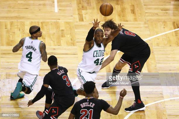Al Horford of the Boston Celtics makes a pass over Jimmy Butler of the Chicago Bulls and Robin Lopez during the fourth quarter of Game One of the...