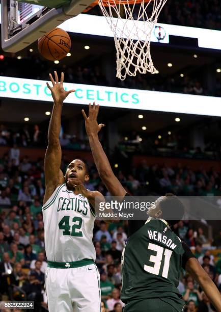 Al Horford of the Boston Celtics takes a shot over John Henson of the Milwaukee Bucks during the fourth quarter at TD Garden on October 18 2017 in...