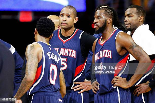 Al Horford talks to DeMarre Carroll and Jeff Teague of the Atlanta Hawks prior to being ejected from the game for a flagrant foul in the second...