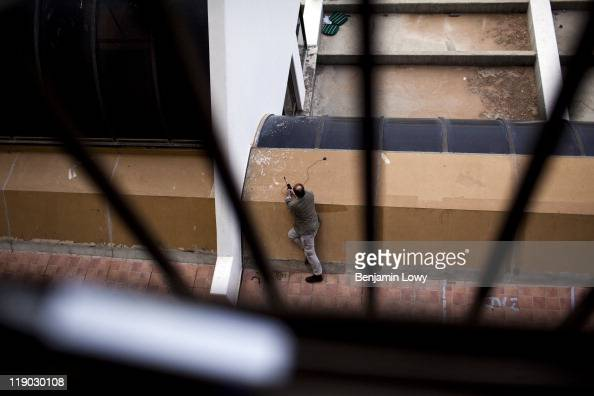 Al Jazeera reporter James Bays peaks over the edge of a hotel terrace while using and iridium sat phone during an early morning shelling of Bengazi...