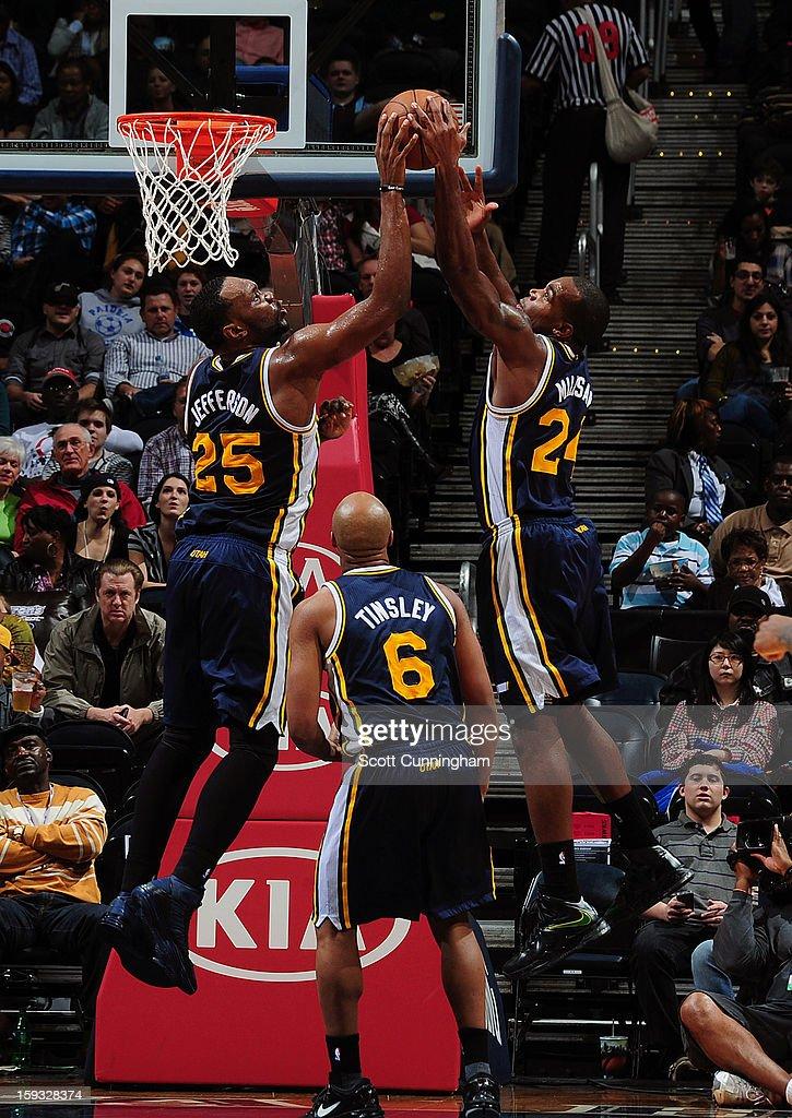 Al Jefferson #25 and Paul Millsap #24 of the Utah Jazz go up for the rebound against the Atlanta Hawks on January 11, 2013 at Philips Arena in Atlanta, Georgia.