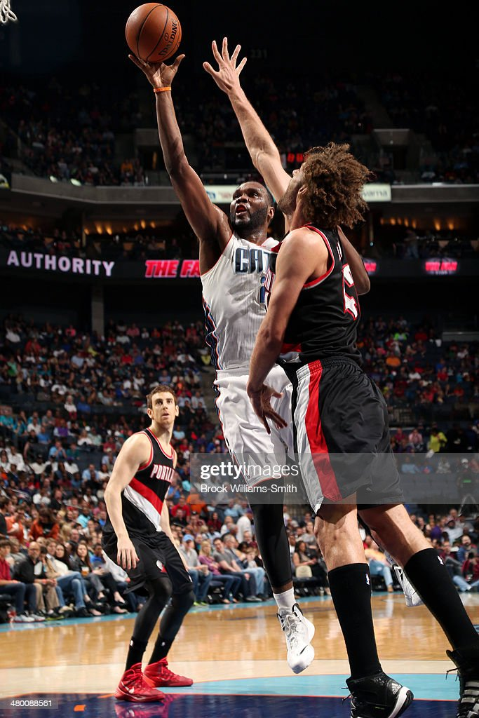 Al Jefferson #25 of the Charlotte Bobcats shoots against Robin Lopez #42 of the Portland Trail Blazers at the Time Warner Cable Arena on March 22, 2014 in Charlotte, North Carolina.