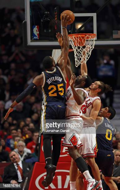 Al Jefferson of the Utah Jazz dinbks over Nazr Mohammed and Joakim Noah of the Chicago Bulls at the United Center on March 8 2013 in Chicago Illinois...