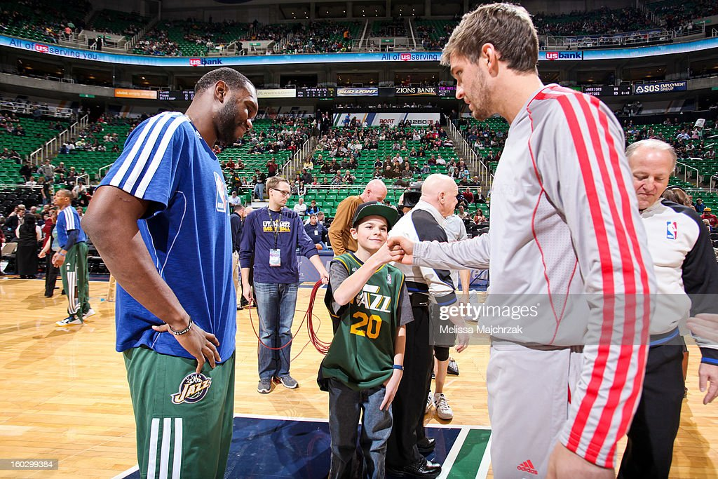Al Jefferson #25 of the Utah Jazz, left, and Chandler Parsons #25 of the Houston Rockets meet with a young fan before their game at Energy Solutions Arena on January 28, 2013 in Salt Lake City, Utah.