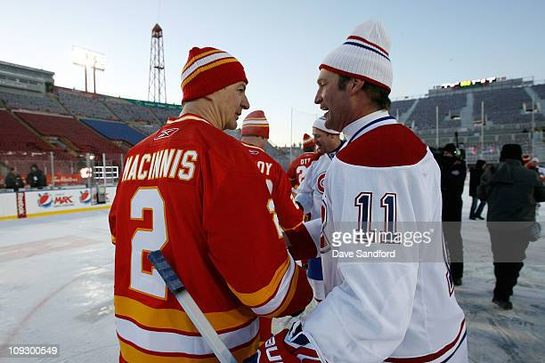 Al MacInnis of the Calgary Flames Alumni shakes hands with Kirk Muller of the Montreal Canadiens Alumni team after the 2011 Tim Hortons Heritage...
