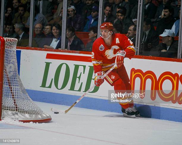 Al MacInnis of the Calgary Flames skates behind the net with the puck against the Montreal Canadiens Circa 1990 at the Montreal Forum in Montreal...