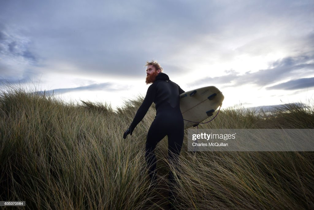 Al Mennie glances back at the shore after catching a few evening waves on February 12, 2017 in Castlerock, Northern Ireland. As the daylight hours begin to stretch the thawing sunshine suggests the onset of Spring and the end of another surf season.