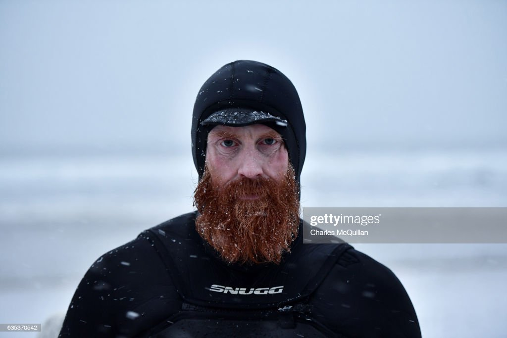Al Mennie is photographed as he makes his way towards the water at east strand beach during a snow storm on January 12, 2017 in Portrush, Northern Ireland. Winter surfing is a pursuit for the robust of soul assisted only by a thermal wetsuit, boots and gloves. The neoprene custom made design can be twice as thick compared to its summer counterpart. Even with these advancements in equipment mangled fingers and frozen feet are still typical.