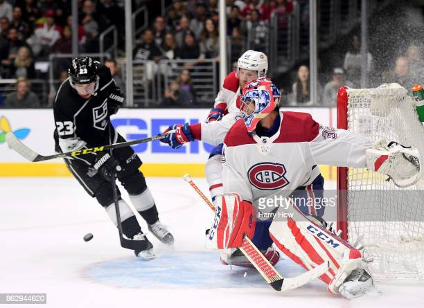 Al Montoya of the Montreal Canadiens reacts as a Dustin Brown of the Los Angeles Kings misses a centering pass as he is checked by Karl Alzner during...