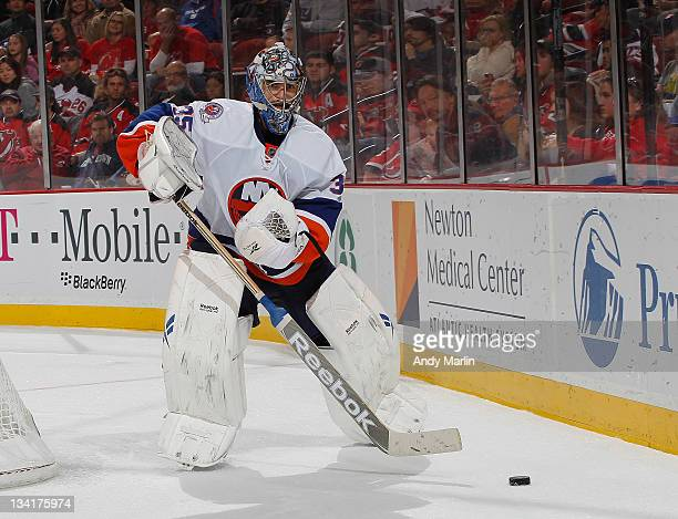 Al Montoya of the New York Islanders plays the puck against the New Jersey Devils during the game at the Prudential Center on November 26 2011 in...
