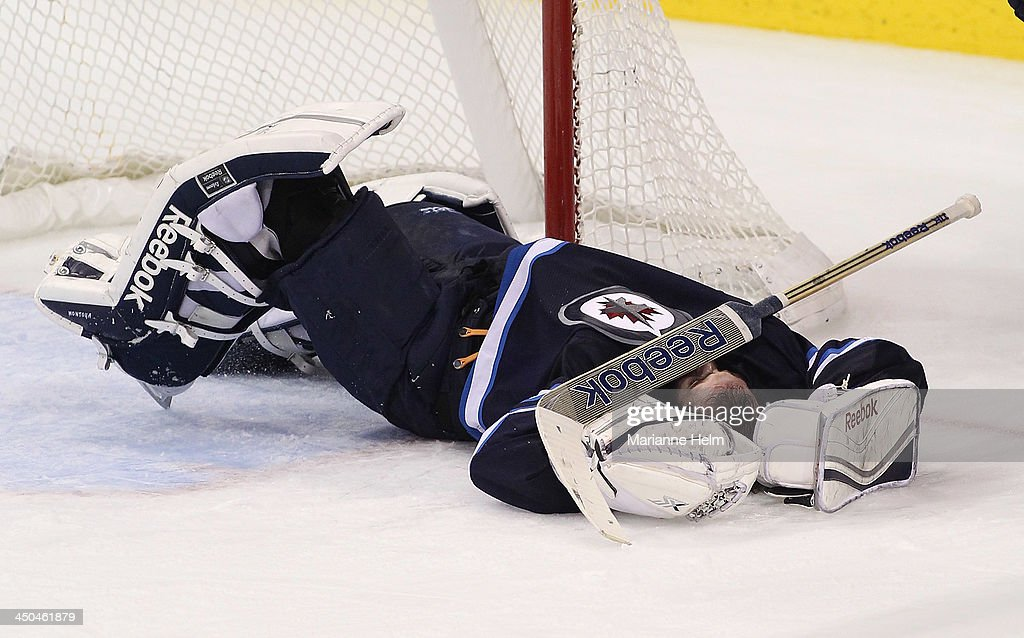 <a gi-track='captionPersonalityLinkClicked' href=/galleries/search?phrase=Al+Montoya&family=editorial&specificpeople=213916 ng-click='$event.stopPropagation()'>Al Montoya</a> #35 of the Winnipeg Jets lays on the ice hurt after Lee Stempniak #22 of the Calgary Flames tripped over him in third period action in an NHL game at the MTS Centre on November 18, 2013 in Winnipeg, Manitoba, Canada.