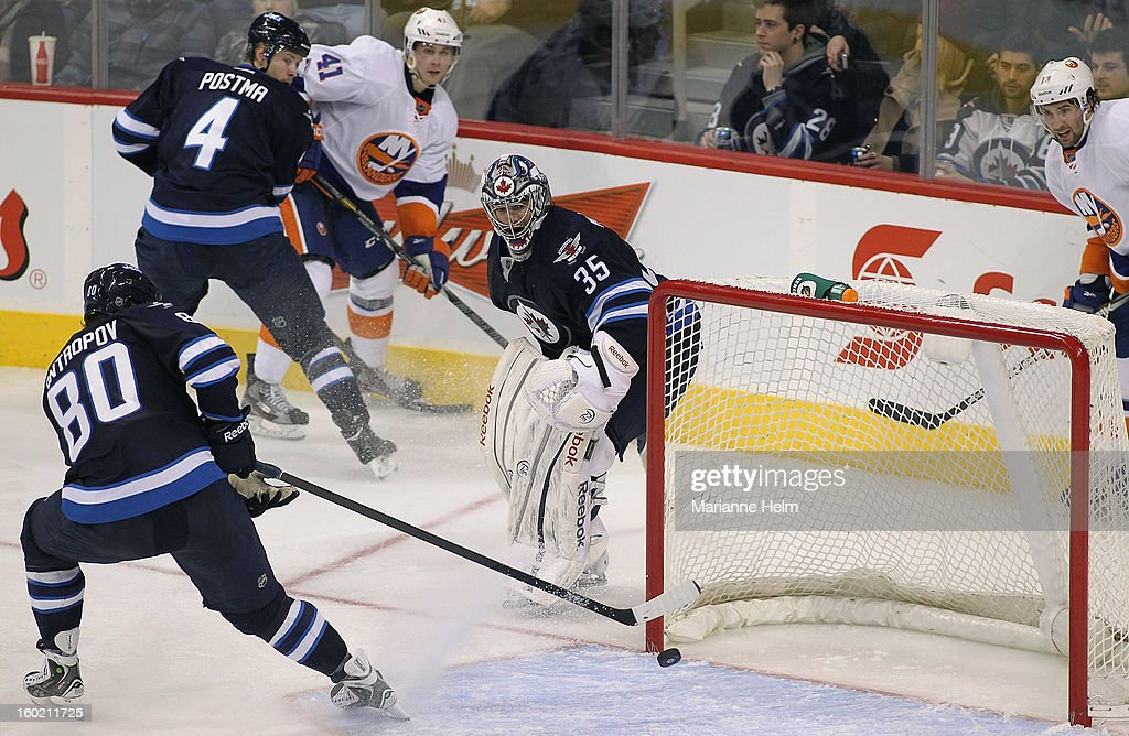<a gi-track='captionPersonalityLinkClicked' href=/galleries/search?phrase=Al+Montoya&family=editorial&specificpeople=213916 ng-click='$event.stopPropagation()'>Al Montoya</a> #35 of the Winnipeg Jets looks back as teammate <a gi-track='captionPersonalityLinkClicked' href=/galleries/search?phrase=Nik+Antropov&family=editorial&specificpeople=202953 ng-click='$event.stopPropagation()'>Nik Antropov</a> #80 helps him out with an empty net in a game against the New York Islanders in third period action on January 27, 2013 at the MTS Centre in Winnipeg, Manitoba, Canada.