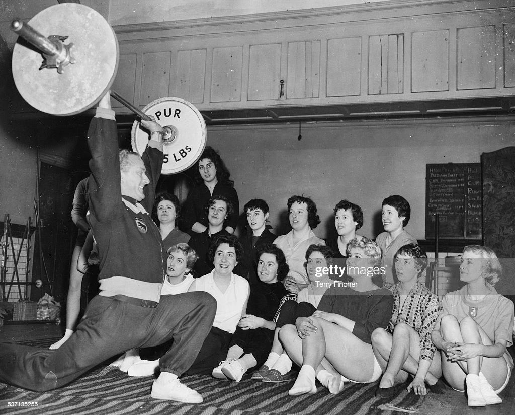 Al Murray weight lifting coach of the British National team performing a clean and jerk with a barbell weight in front of a group of office girls at...