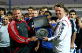 Al Nasr's head coach Frank Pagelsdorf hands over a trophy to Bayern's head coach Louis van Gaal of Bayern Muenchen during the FC Bayern Muenchen...