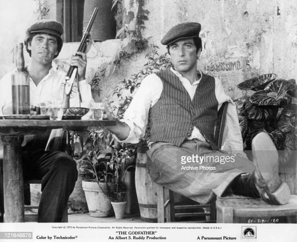 Al Pacino sits at a table with an unknown actor that has a gun in his hand in a scene from the film 'The Godfather' 1972