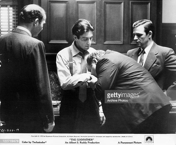 Al Pacino stands as Richard S Castellano kisses his hand in a scene from the film 'The Godfather' 1972