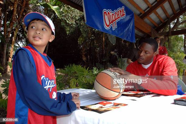 Al Thornton of the Los Angeles Clippers autographs a basketball for a young fan during the Clippers Community Kids Block Party at Knott's Berry Farm...