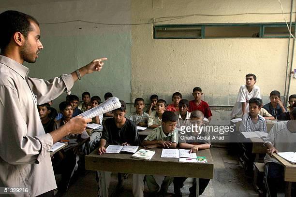 Ala'a Ali a teacher in the Qaim Madrassa a koranic school explain to a student how to a recite properly in the Shiite slums of Sadr City August 2...