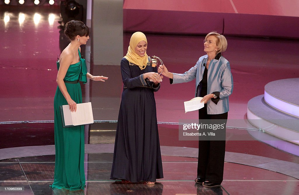 Alaa Murabit (C) receives Bellisario award from Foreign Minister Emma Bonino (R) during the Premio Bellisario 2013 at Dear RAI studios on June 20, 2013 in Rome, Italy.