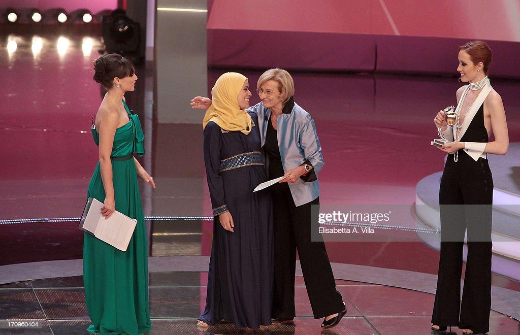 Alaa Murabit (C) receives Bellisario award from Foreign Minister Emma Bonino (2nd R) during the Premio Bellisario 2013 at Dear RAI studios on June 20, 2013 in Rome, Italy.
