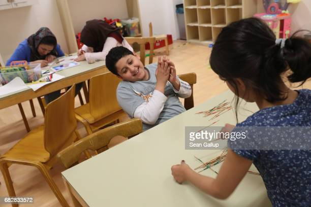 Alaa who is from Lebanon takes delight in playing mikado with Parisa from Afghanistan at the shelter for refugees and migrants where they live in...