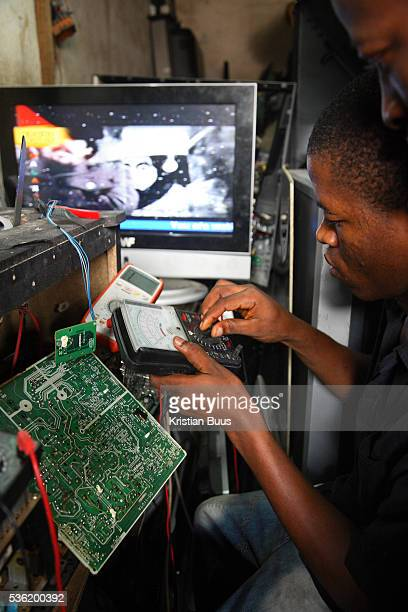 Alaba International Market A young man is fixing and testing old broken tvs New and old and a lot of nonworking electronic goods such as TVs and...